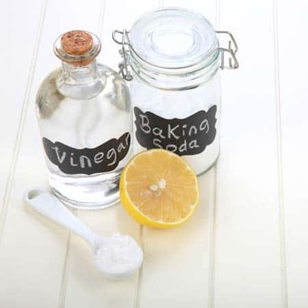 ingredients for making a spray for cleaning a yoga mat-soda, spoon, lemon and water
